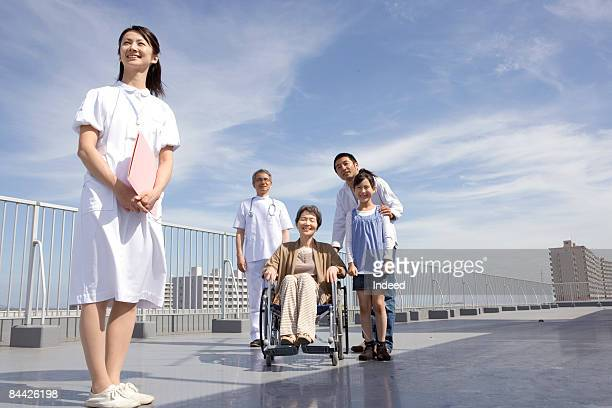 Nurse, doctor, and patient family smiling