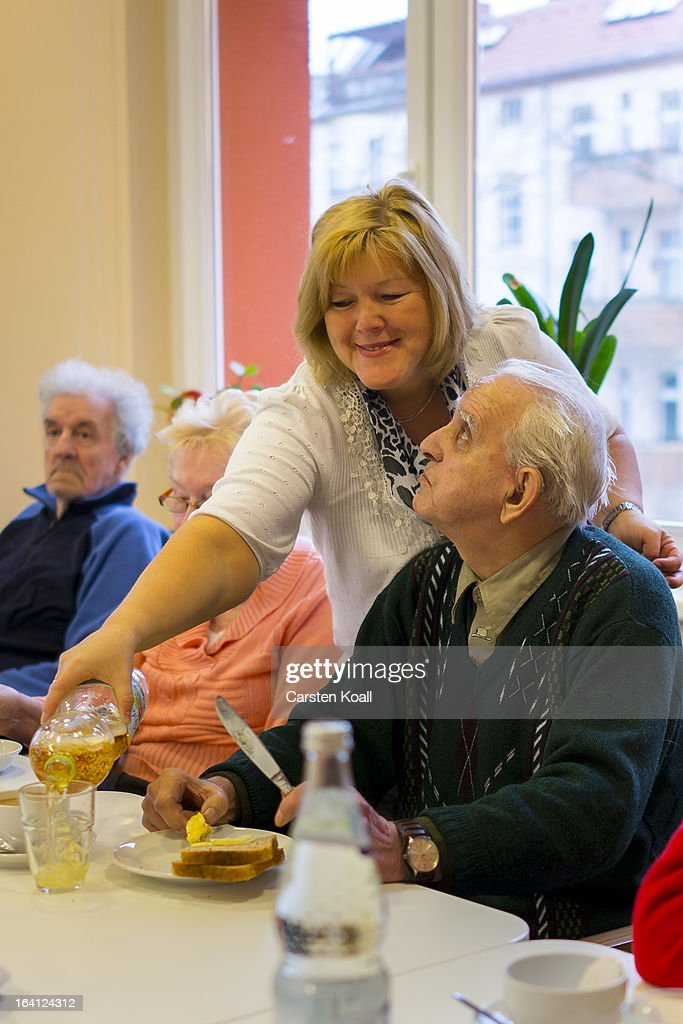 Nurse Doret Kohl (C) talks with day guest Werner (R) during the midday meal in the geriatric day care facility of the German Red Cross (DRK, or Deutsches Rotes Kreuz) at Villa Albrecht on March 18, 2013 in Berlin, Germany. A great number of senior Citzens struggle with various forms of dementia at Villa Albrecht. The German Red Cross dates its origin back to 1863 with the founding of the Wuerttembergischer Sanitaetsverein, a medical association that provided care to wounded soldiers. Today the German Red Cross has four million members nationwide and is active in international aid and social care.