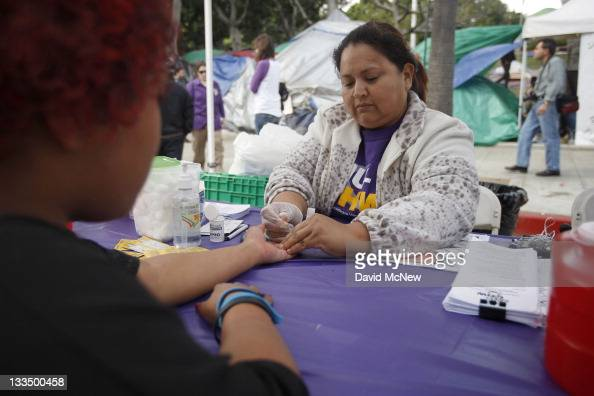 Nurse Enedina Rosas takes a blood sample for a glucose test at the Healthcare for the 99% Health Fair organized by the United Healthcare Workers...