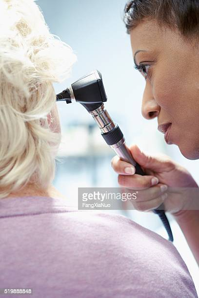 Nurse examining a patient's ear