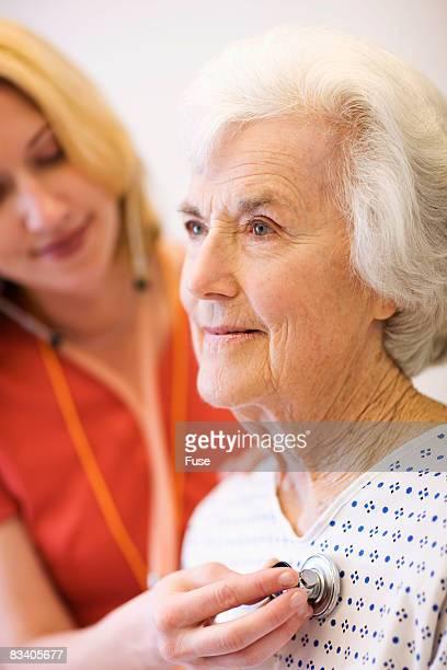 Nurse Examining Elderly Patient
