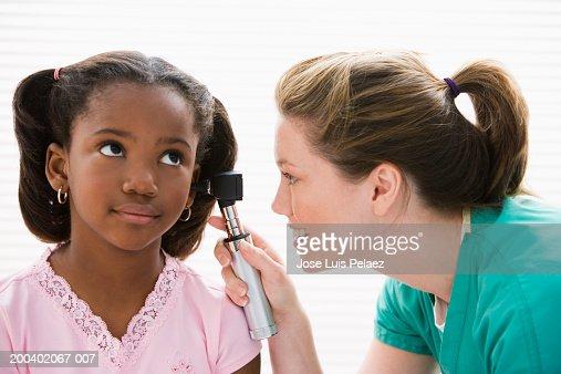 Nurse examining girl (8-10) with otoscope : Stock Photo