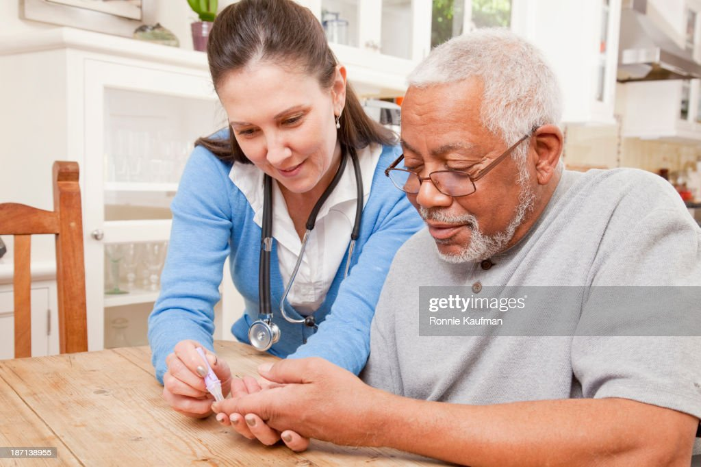 Nurse examining older patient in home