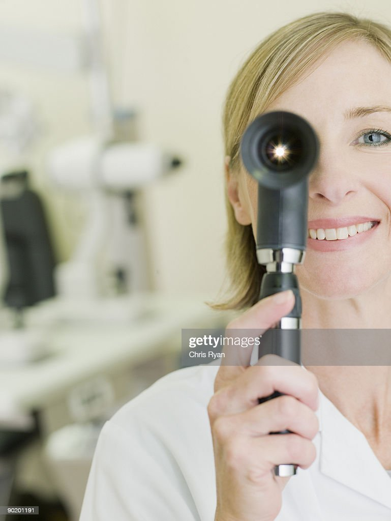 Nurse examining patient with opthalmoscope