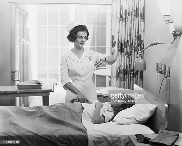 Nurse examining temperature and taking pulse of girl