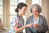 Nurse explaining medication to patient in home