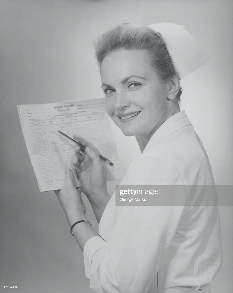 Nurse filling medical chart in studio, (B&W), portrait : Stock Photo