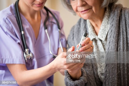 Nurse giving blood sugar test to patient in home