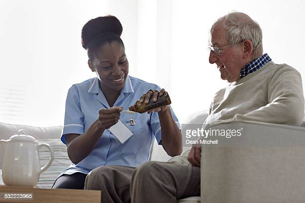 Nurse giving medicinal syrup to elderly man at home