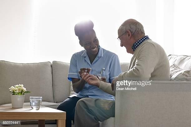Krankenschwester gibt Medikament, senior Patienten wie zu Hause fühlen.