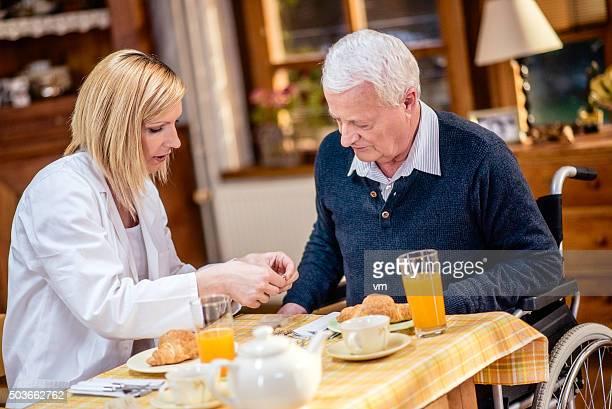 Enfermera dando píldoras a un hombre mayor