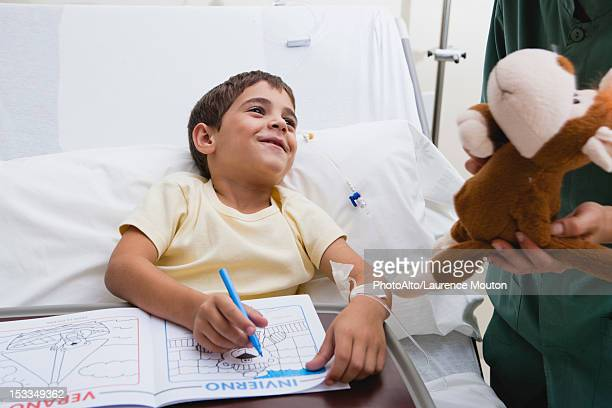 Nurse giving sick boy stuffed animal in hospital, cropped
