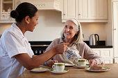 Nurse having tea with older woman