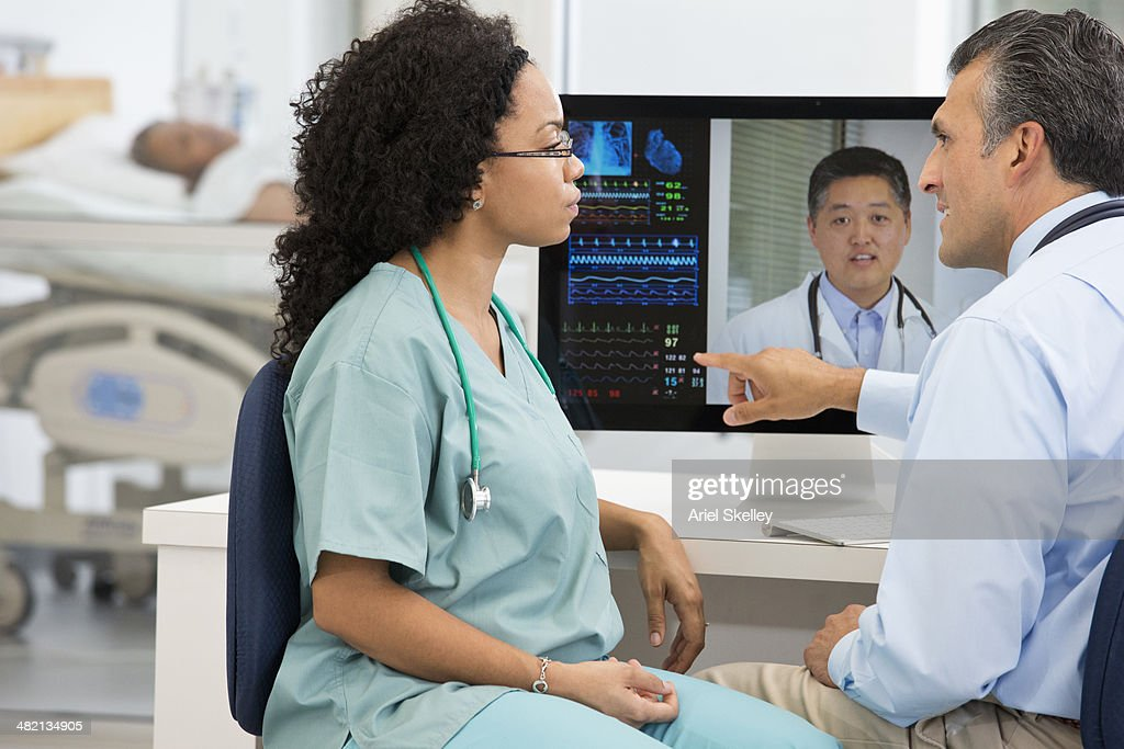 Nurse having teleconference with doctors in hospital : Stock Photo