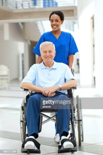 Krankenschwester Unterstützung eines Patienten im Rollstuhl