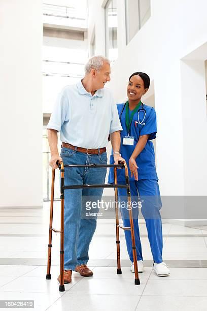 Enfermera ayudar a un paciente con walker