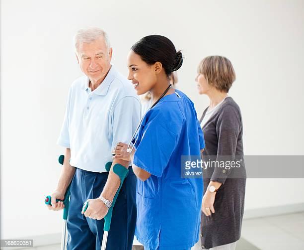 Enfermera ayudar a un paciente senior en crutches