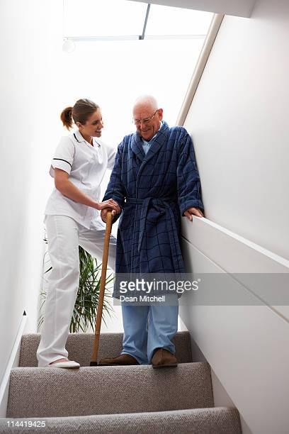 Krankenschwester hilft ein älterer Mann hinunter Treppe