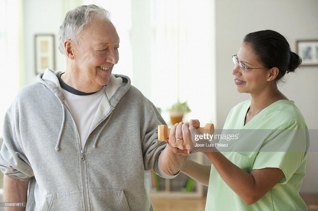 Nurse helping elderly man lift weights : Stock Photo
