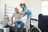 Smiling nurse assisting senior man to get up from bed. Caring nurse supporting patient while getting up from bed and move towards wheelchair at home. Helping elderly disabled man standing up in his be