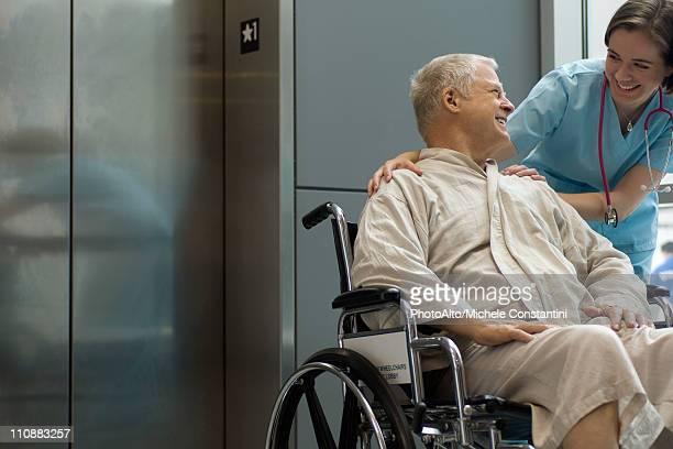 Nurse helping patient in wheelchair