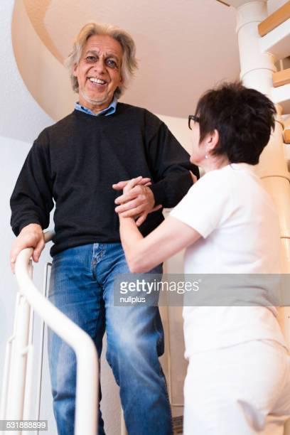 Krankenschwester helfen senior Mann klettert Treppe