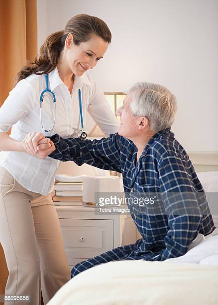 Nurse helping senior man out of man