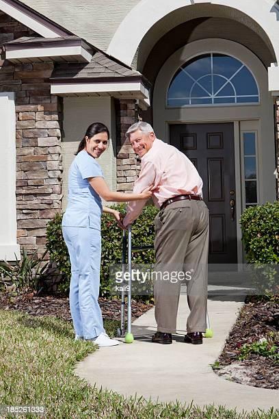 Infirmière aidant senior homme avec walker en face de l'hôtel