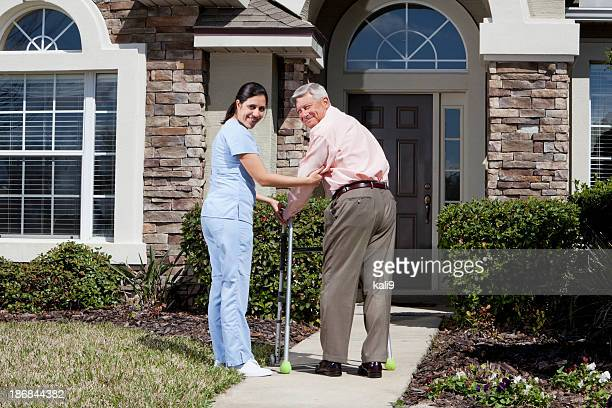 Nurse helping senior man with walker in front of house