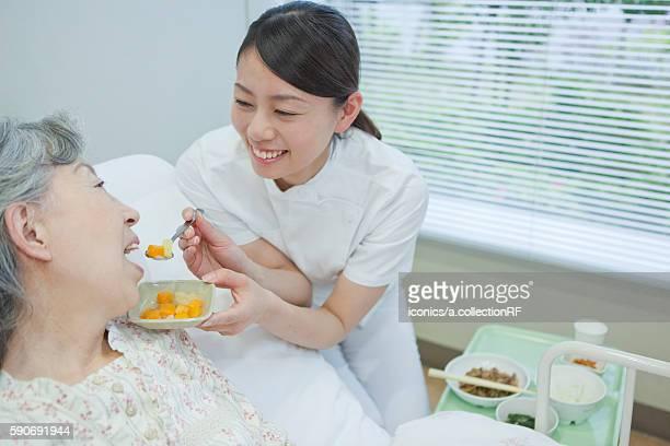Nurse helping senior woman eat food, Kanagawa Prefecture, Honshu, Japan