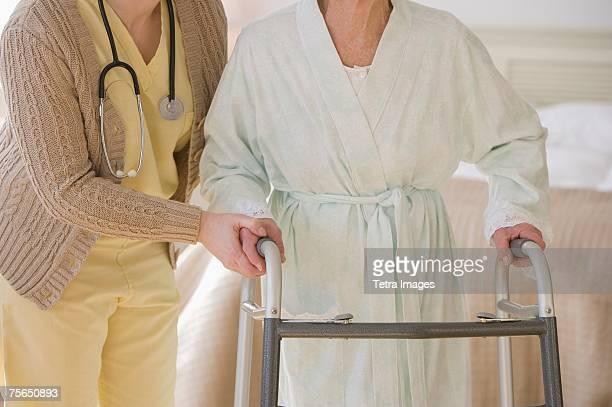 Nurse helping senior woman use walker