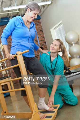 Friendly nurse assisting senior lady with physical therapy