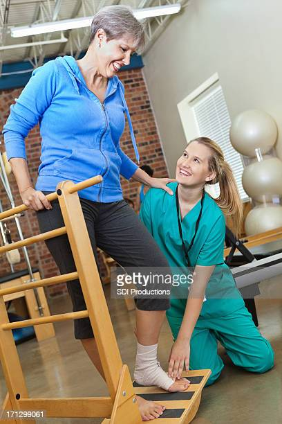Nurse helping senior woman with physical therapy