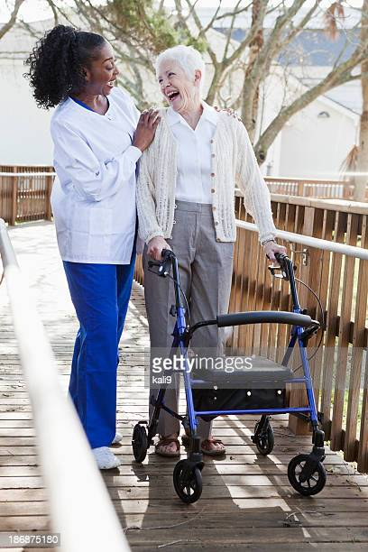 Nurse helping senior woman with walker