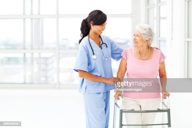 Infirmière aide Femme âgée avec Walker tout en regardant son