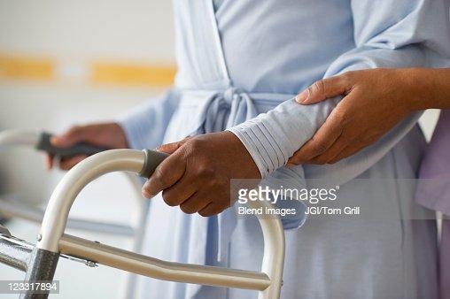 Nurse helping woman use walker in hospital hallway