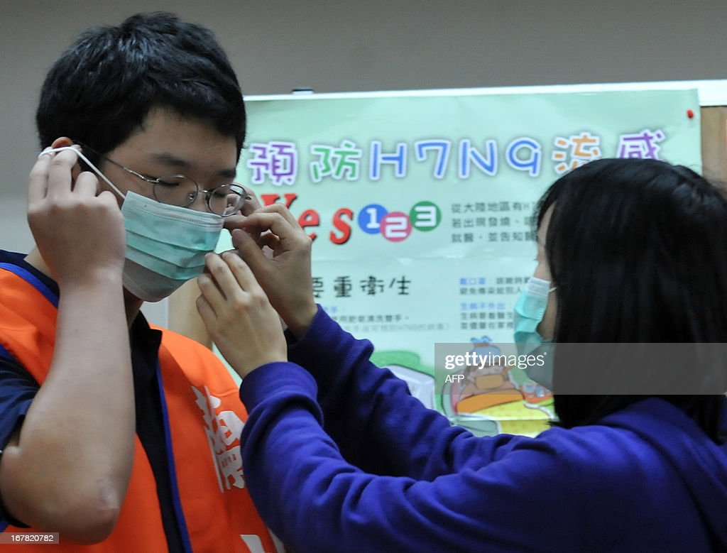 A nurse helps a student (L) to wear a mask correctly in a junior high school in Taipei on May 1, 2013. The deadly H7N9 bird flu strain claimed a new victim when a hospital patient died in China, state media reported, bringing the death toll from the recently identified virus to 24. AFP PHOTO / Mandy CHENG