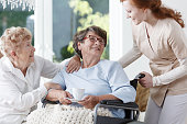 Nurse helps senior woman to move on in senior home during meeting with friend
