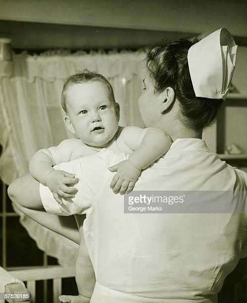 Nurse holding baby boy (6-12 months), (B&W)