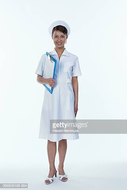 Nurse holding clipboard, smiling, portrait