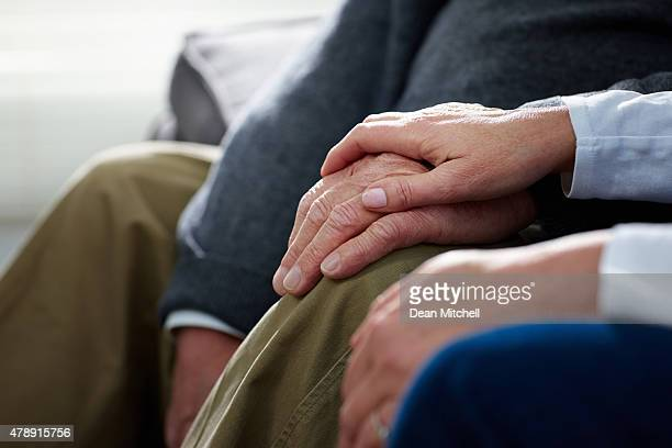 Nurse holding hand of senior male patient