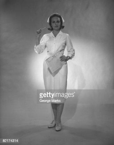 Nurse holding medical chart posing in studio, (B&W), portrait : Bildbanksbilder