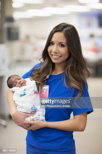 Nurse holding newborn baby in hospital