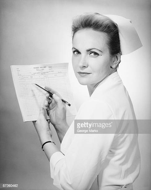 Nurse holding patient's chart in studio, (B&W), portrait