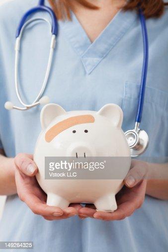Nurse holding piggy bank, midsection