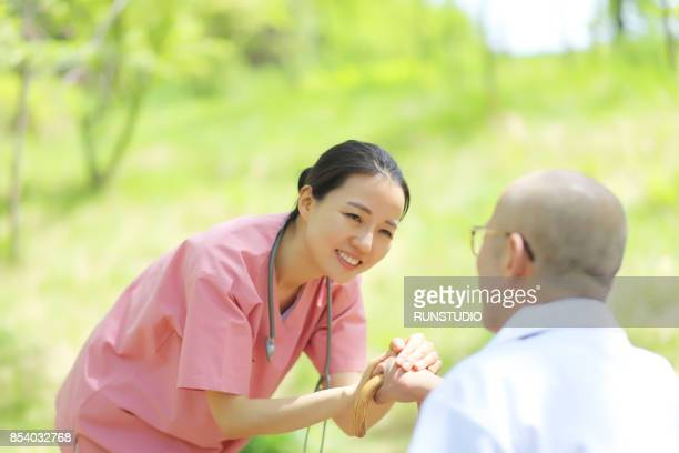 Nurse Holding Senior Man's Hands
