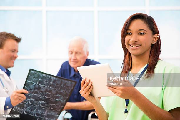 Nurse holds digital tablet. Doctor with senior patient, x-ray background.