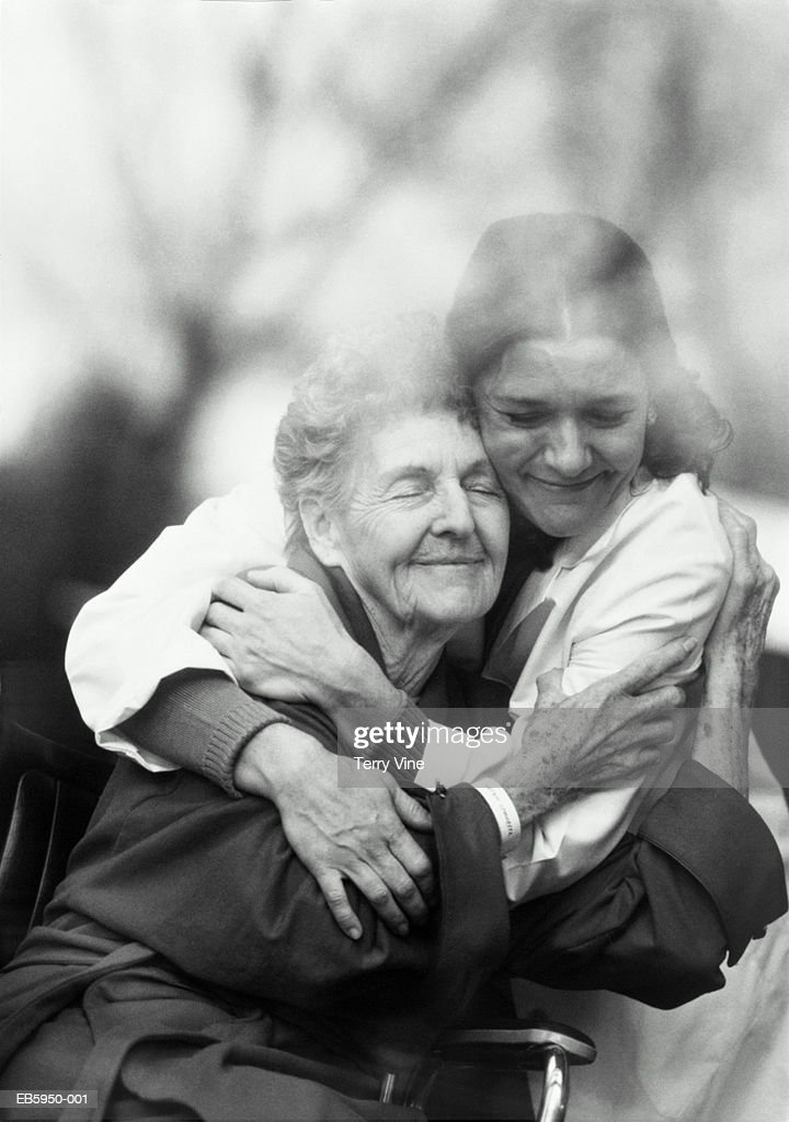 Nurse hugging elderly patient in wheelchair (B&W) : Foto de stock