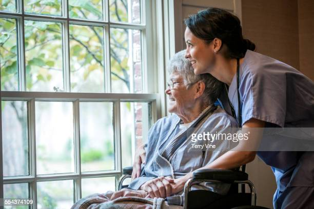 Nurse hugging patient in wheelchair near window