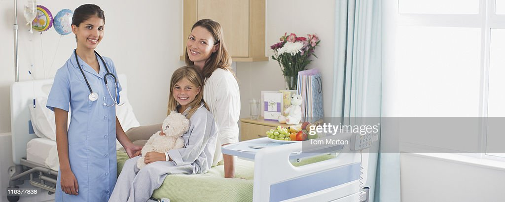 Nurse in childrens hospital with girl patient and mother : Stock Photo